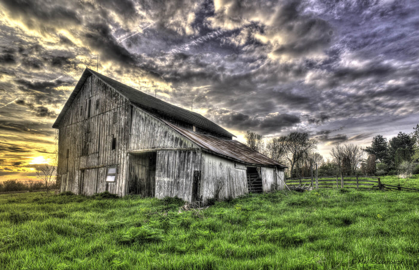 Weathered old barn in bright green field against dramatic cloud sky at sunset, high dynamic range photo - HDR