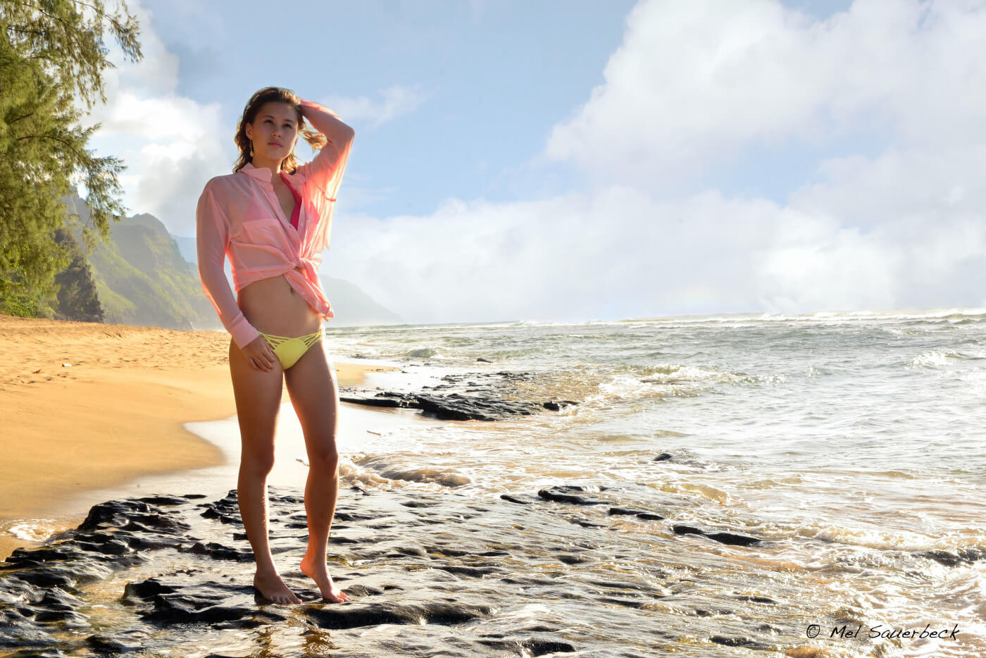 Beautiful young woman, standing in ocean surf, wearing pink blouse and small yellow bikini