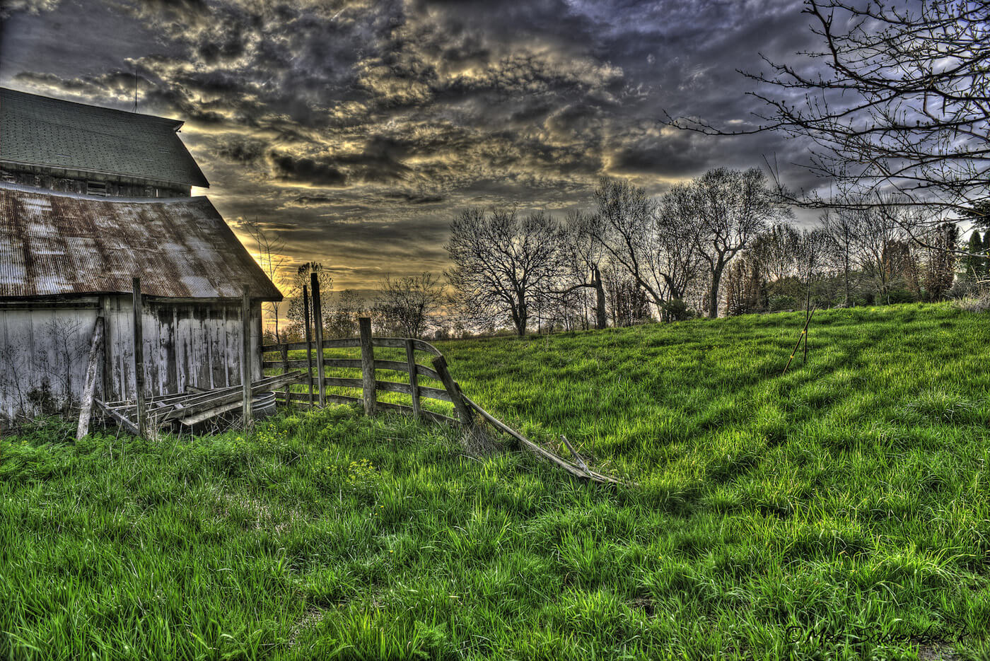 High dynamic range - HDR photo of portion of old barn and falling down fence, with deep green wet grass at sunset. Dramatic clouds overhead