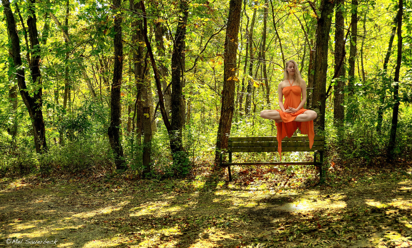 Golden sunset light streaming through trees, Young woman in orange dress sitting in lotus, floating above bench