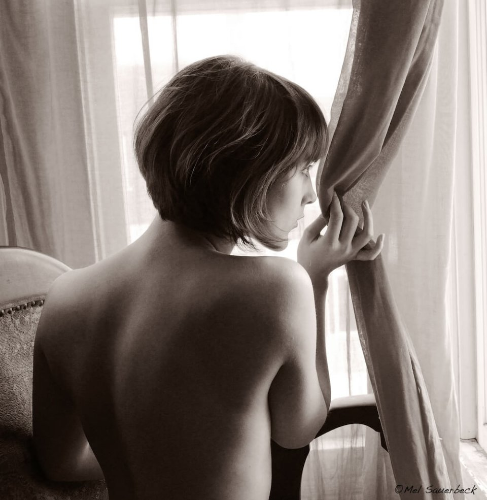 Young woman in chair, with her nude back to camera looks out a curtained window. Black and white photo .
