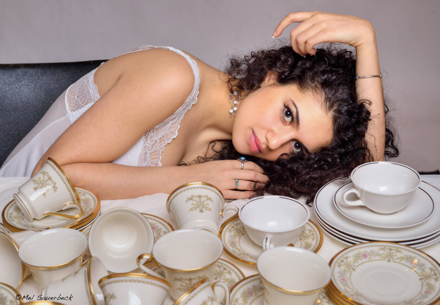 Beautiful dark, curly haired, young woman sitting with many tea cups