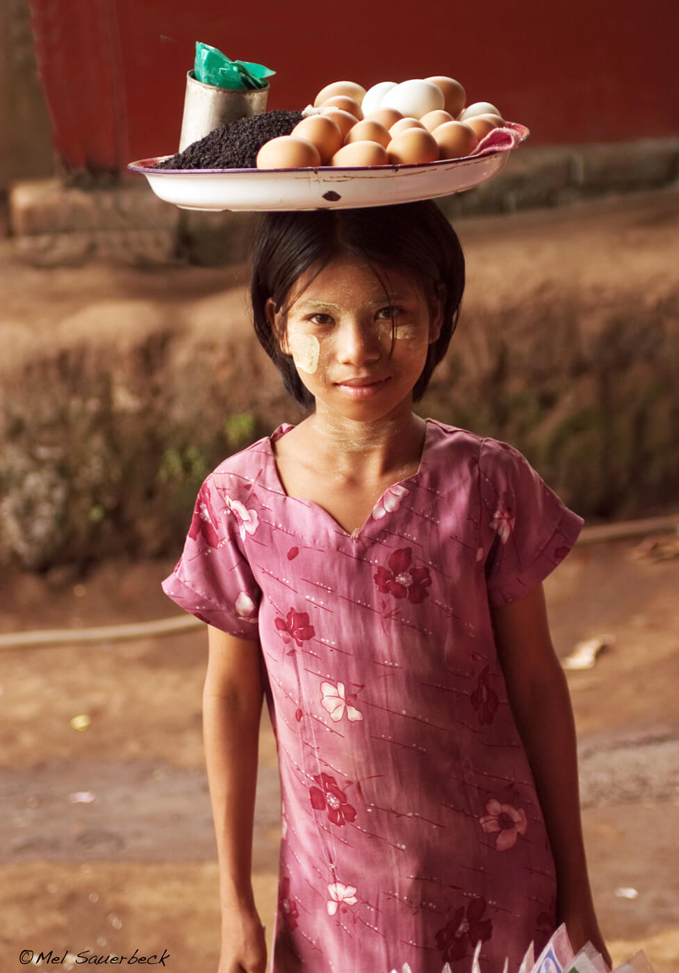 Young girl with tray of food on head, Myanmar