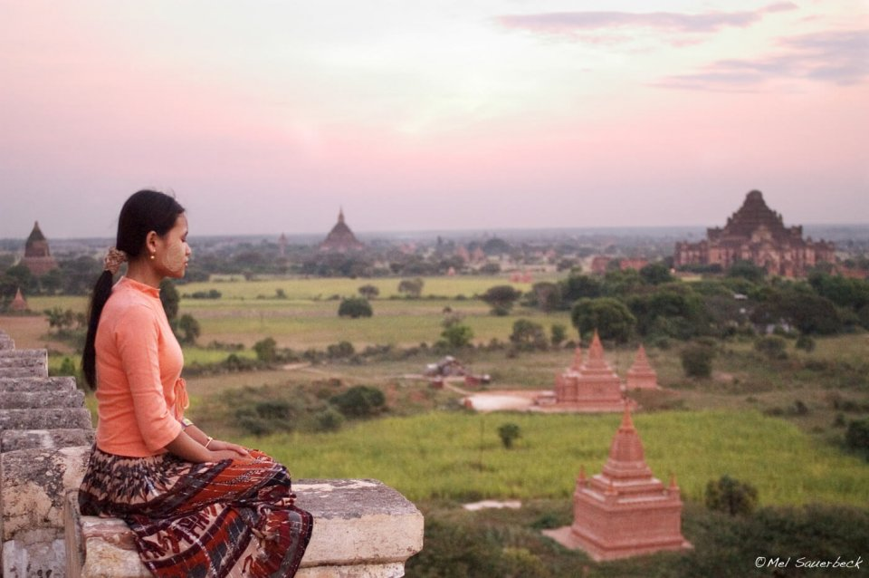 Woman meditating on top of temple, Began, Myanmar, Burma