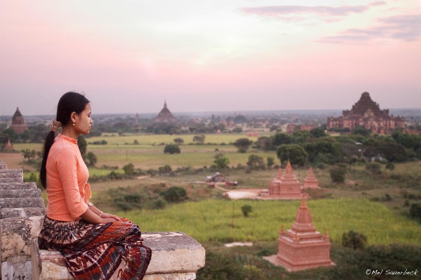 Woman meditating on top of temple, Began, Myanmar, Burma