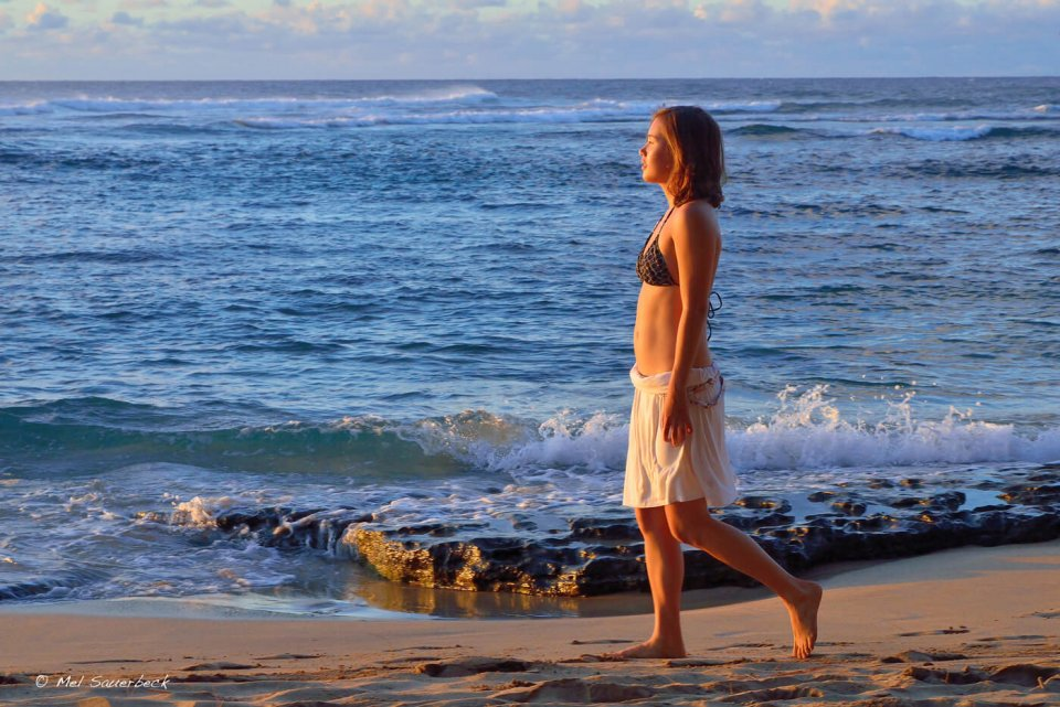 Young woman walking beach, Hawaii