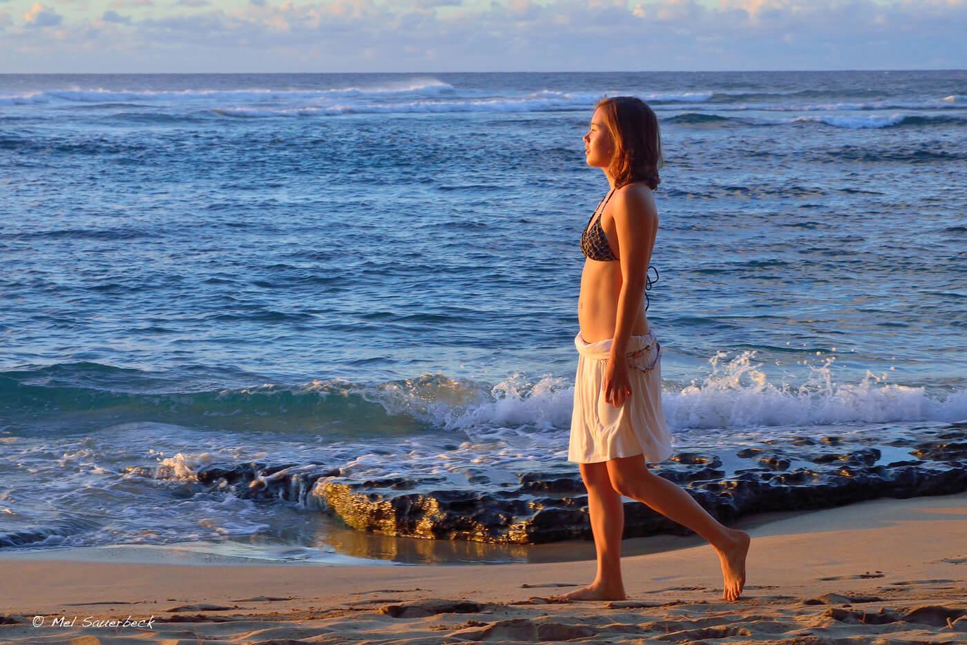 Young woman walking beach, Hawaii