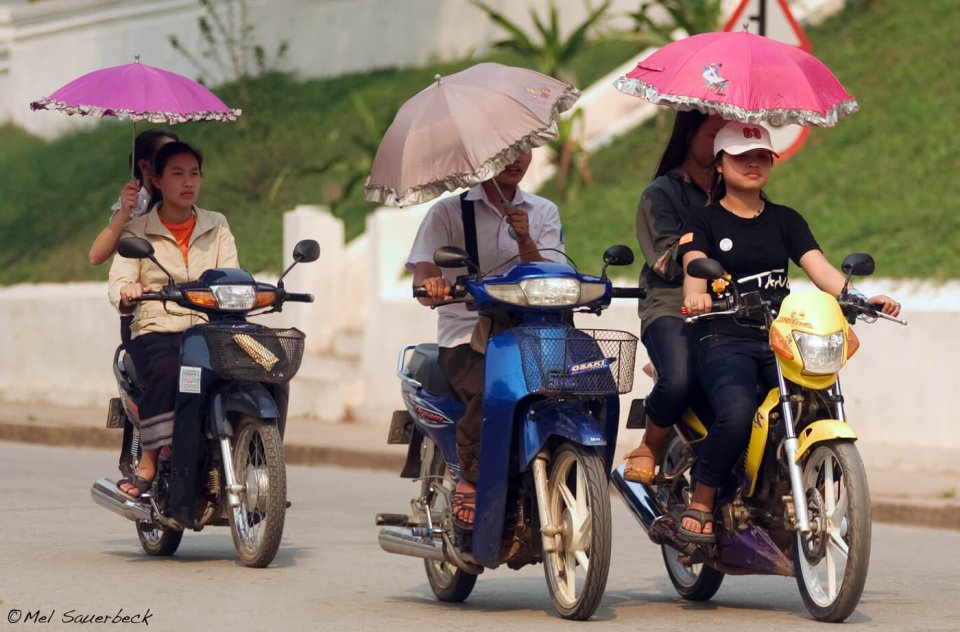 Girls with parasols on scooters, Lao